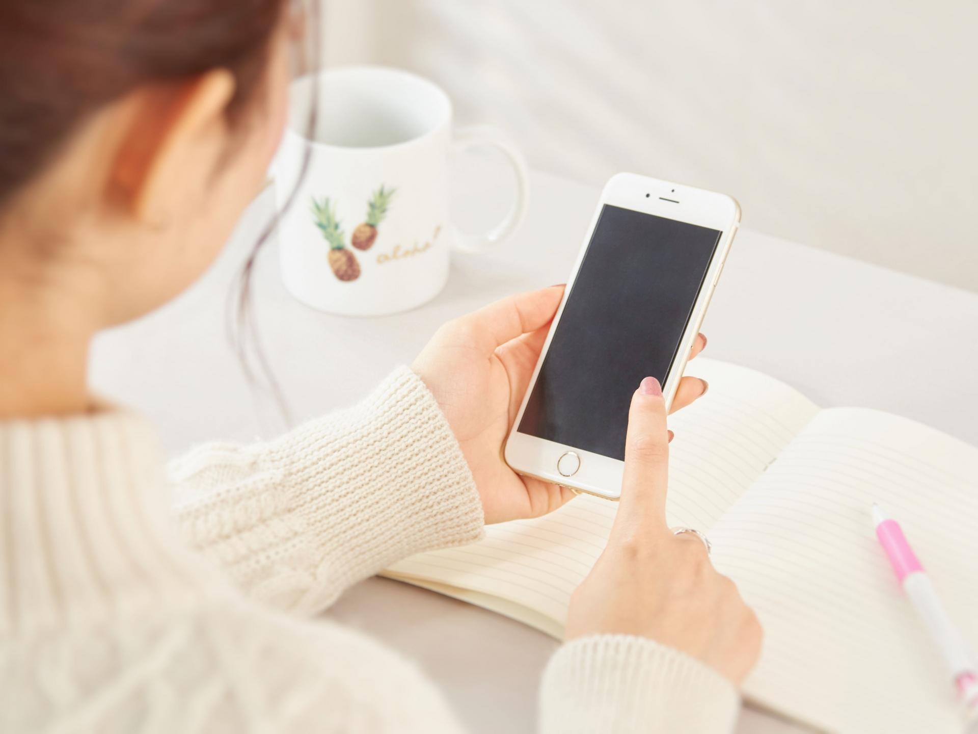 電話を操作する女性の画像